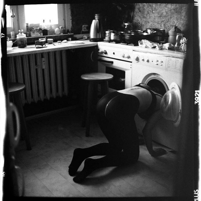 Mujer con cabeza metida en la lavadora